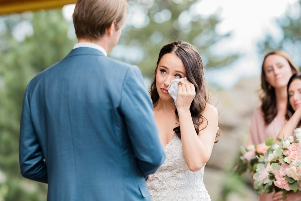 bride wipes away tears during vows Black Canyon Inn wedding by Estes Park wedding photographer Jennie Crate Photographer