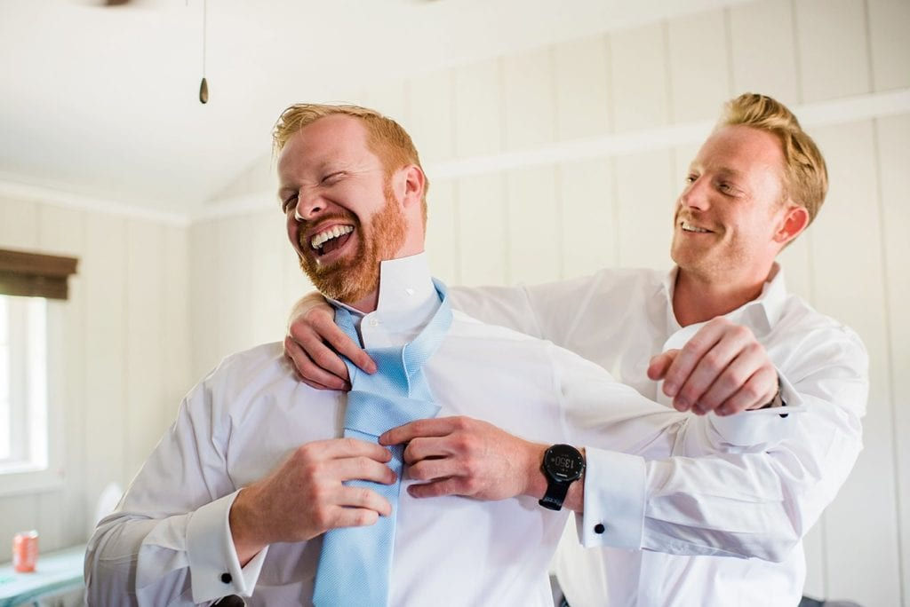 groomsmen tying tie of groom in cabin while getting ready at Grand Lake Lodge wedding by RMNP wedding photographer Jennie Crate