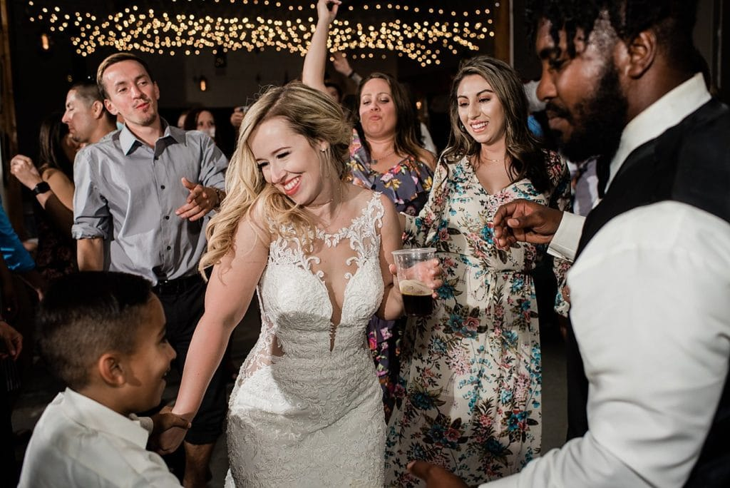 bride dances with guests during wedding reception in barn at at Pagosa Springs wedding by Pagosa Springs Wedding Photographer Jennie Crate