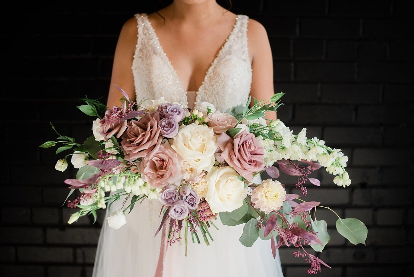 bride with large lavender and rose bridal bouquet in front of black brick wall at at Shyft Denver wedding by Denver wedding photographer Jennie Crate photographer