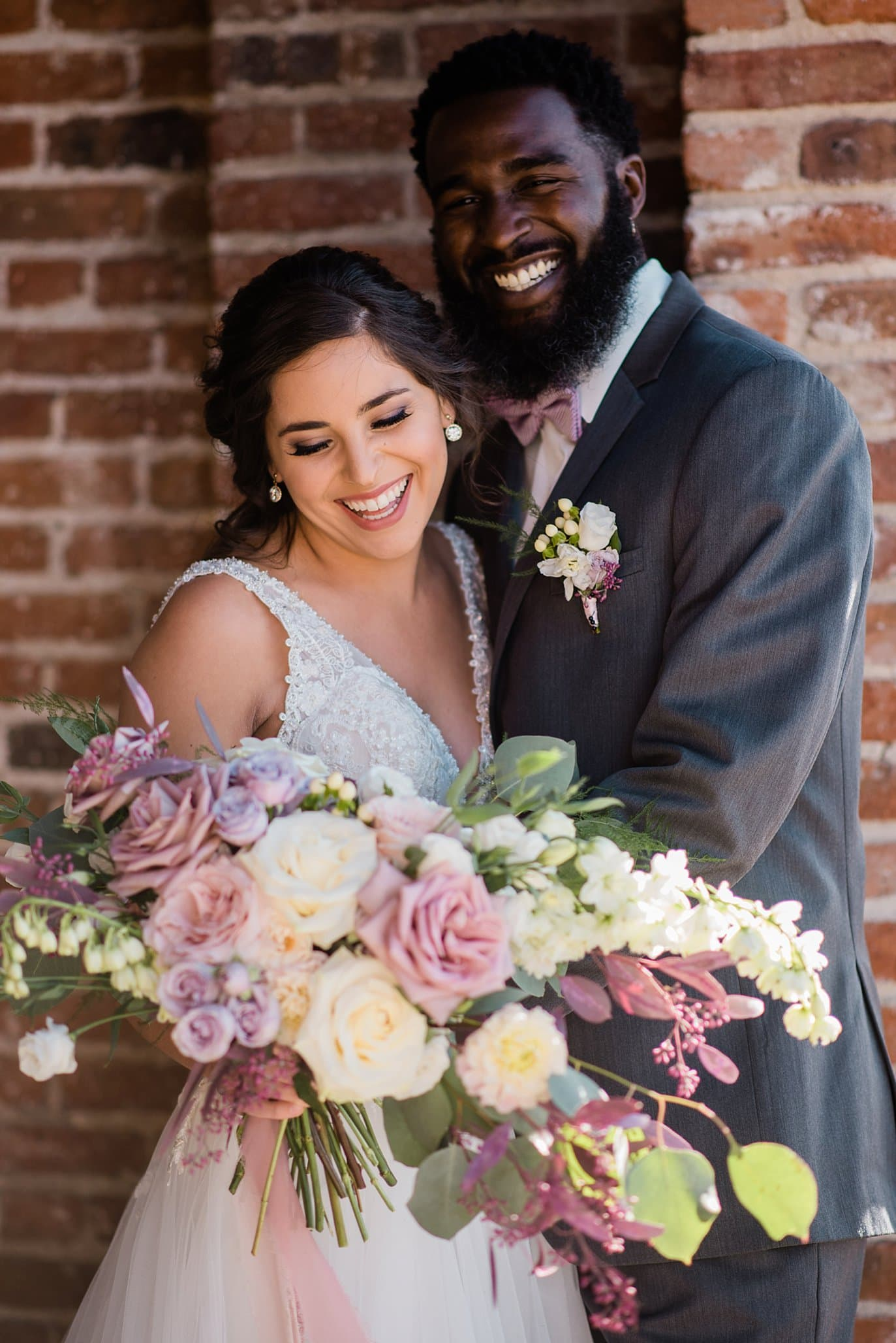 bride and groom smile by brick wall outside STEAM on Platte building at Shyft Denver wedding by Denver wedding photographer Jennie Crate photographer