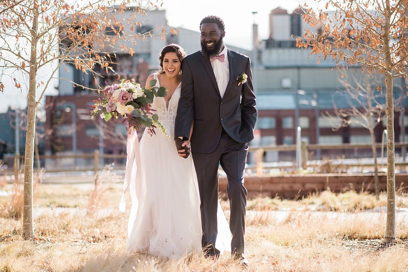 bride and groom walking among trees of industrial space at Shyft Denver wedding by Denver wedding photographer Jennie Crate photographer