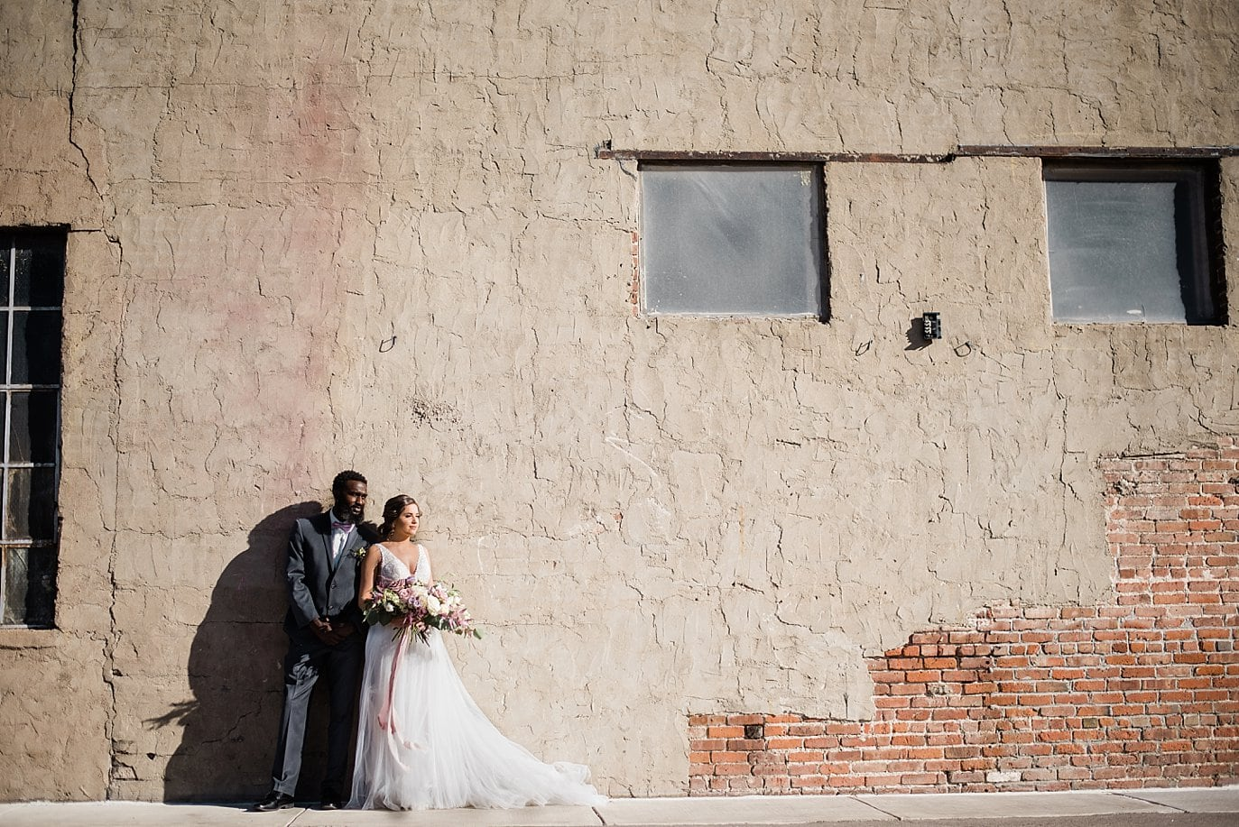 bride and groom by industrial stucco wall at Shyft Denver wedding by Boulder Wedding photographer Jennie Crate photographer