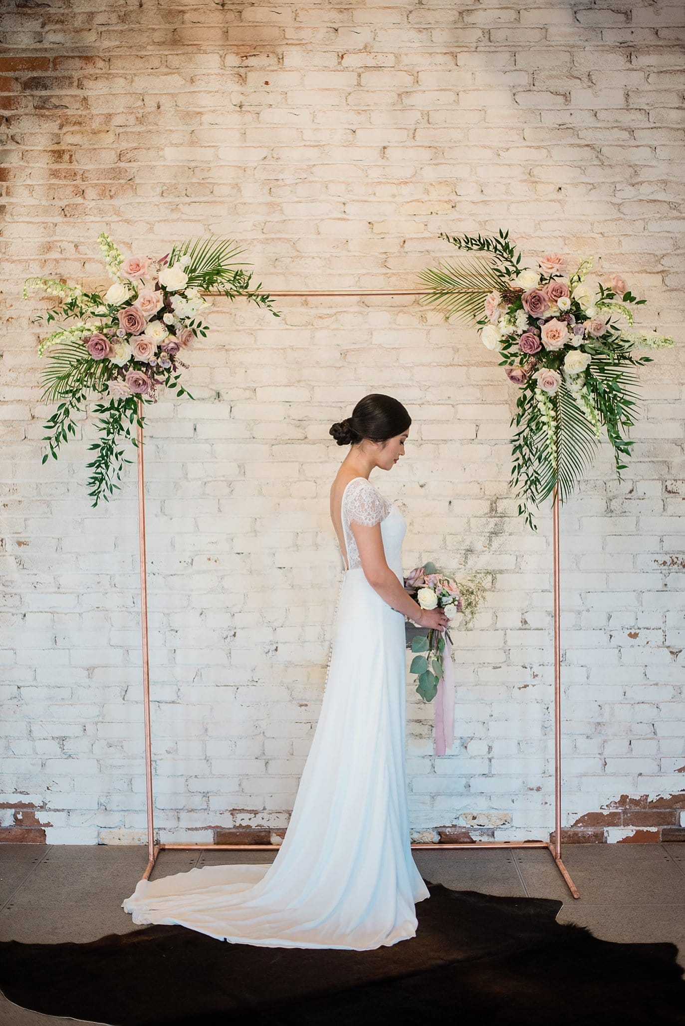 bride in front of copper ceremony arch decorated with rose and violet flowers and green ferns at Shyft Denver wedding by Boulder Wedding photographer Jennie Crate photographer