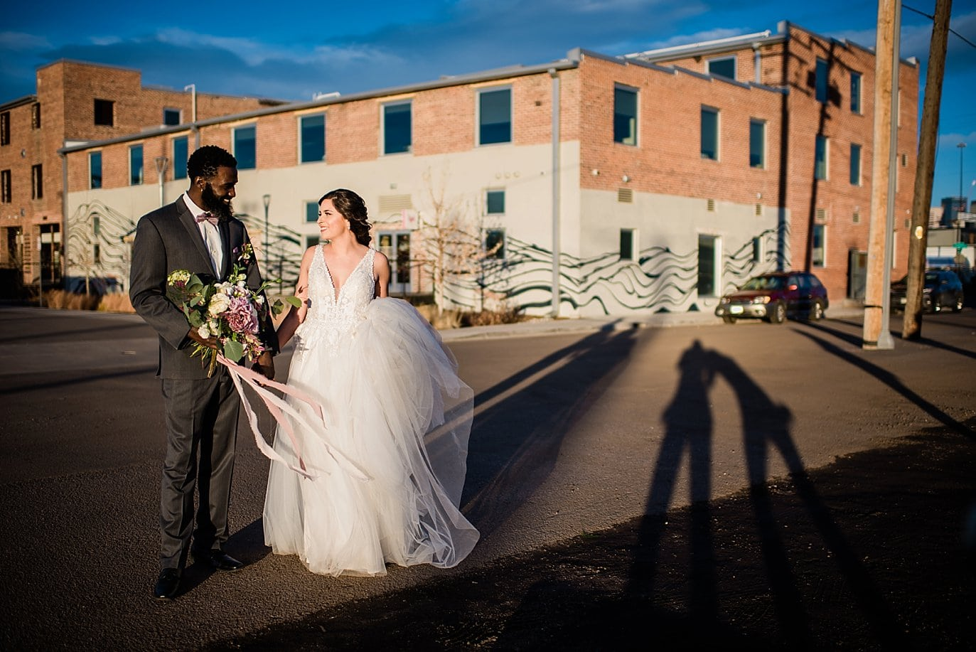 bride and groom walking by STEAM on the Platte building at Shyft Denver wedding by Aurora wedding photographer Jennie Crate photographer