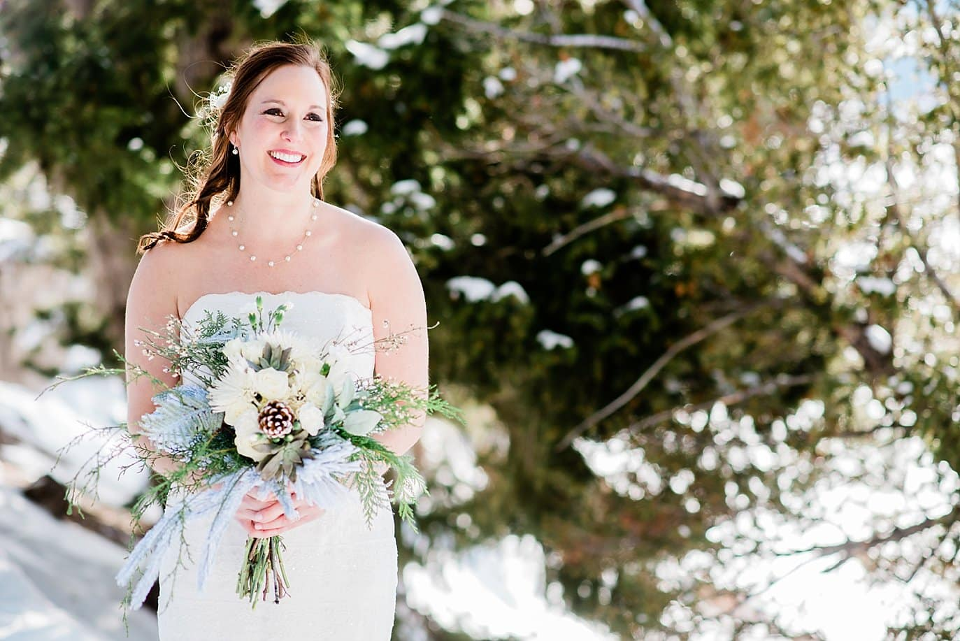 bride in strapless dress with neutral winter flowers at Sapphire Point Elopement by Dillon wedding photographer Jennie Crate Photographer