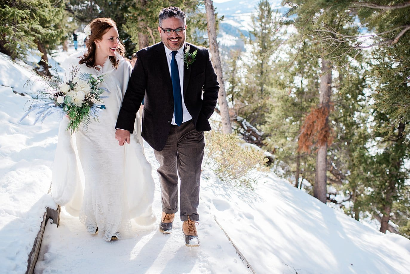 bride and groom walk in snow at Sapphire Point Elopement by Dillon wedding photographer Jennie Crate Photographer
