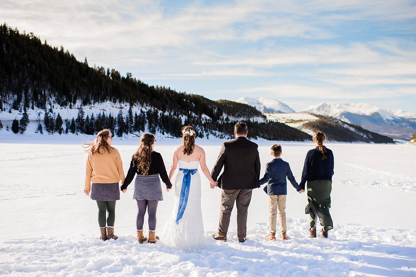 bride and groom and family hold hands on Lake Dillon at Sapphire Point Elopement by Vail wedding photographer Jennie Crate Photographer