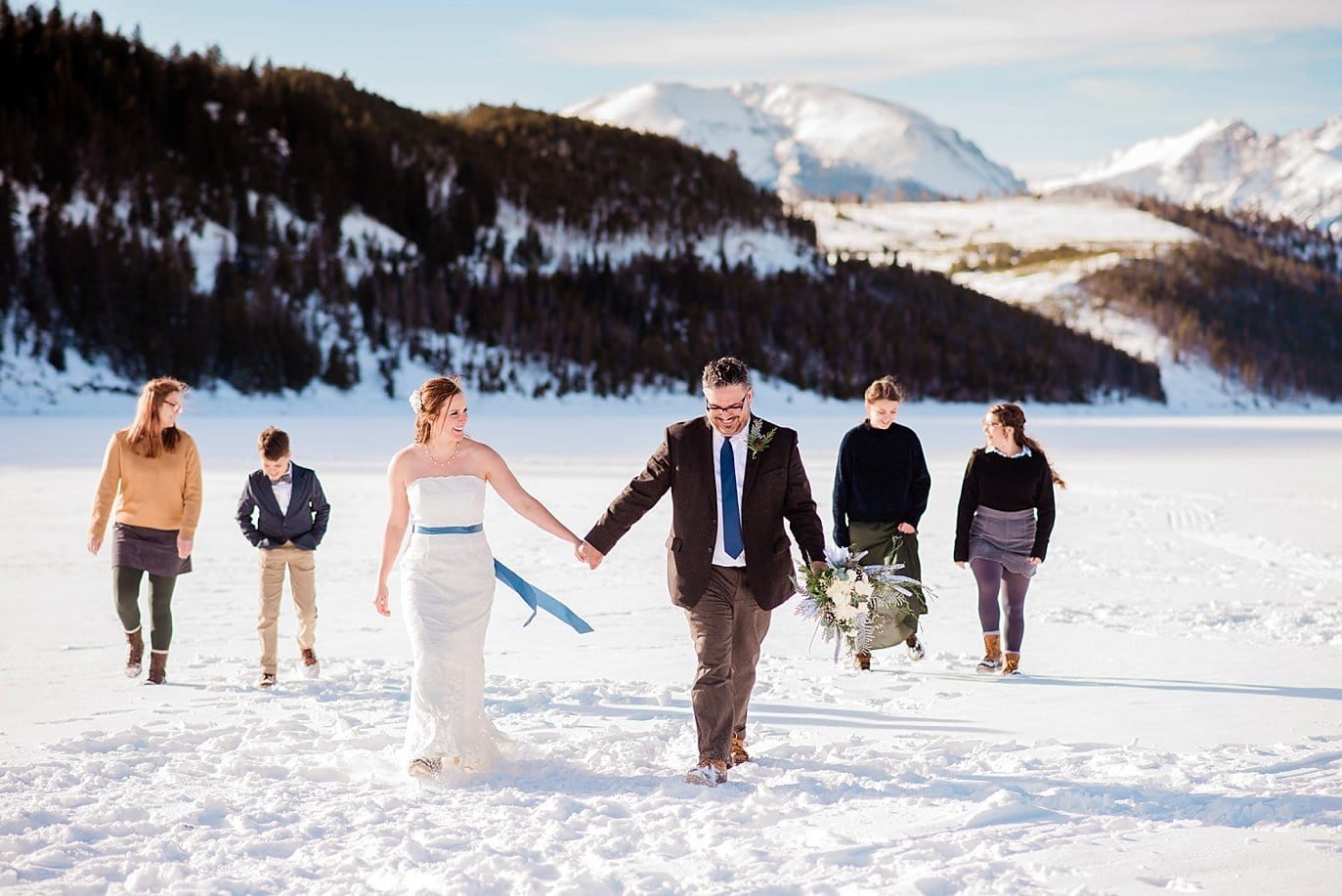bride and groom walk across frozen lake dillon with kids at Sapphire Point Elopement by Vail wedding photographer Jennie Crate Photographer