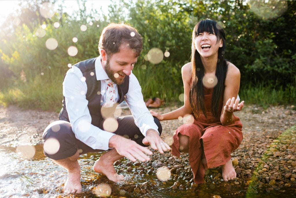 couple plays in creek laughing at RMNP engagement session by Denver Wedding Photographer Jennie Crate Photographer