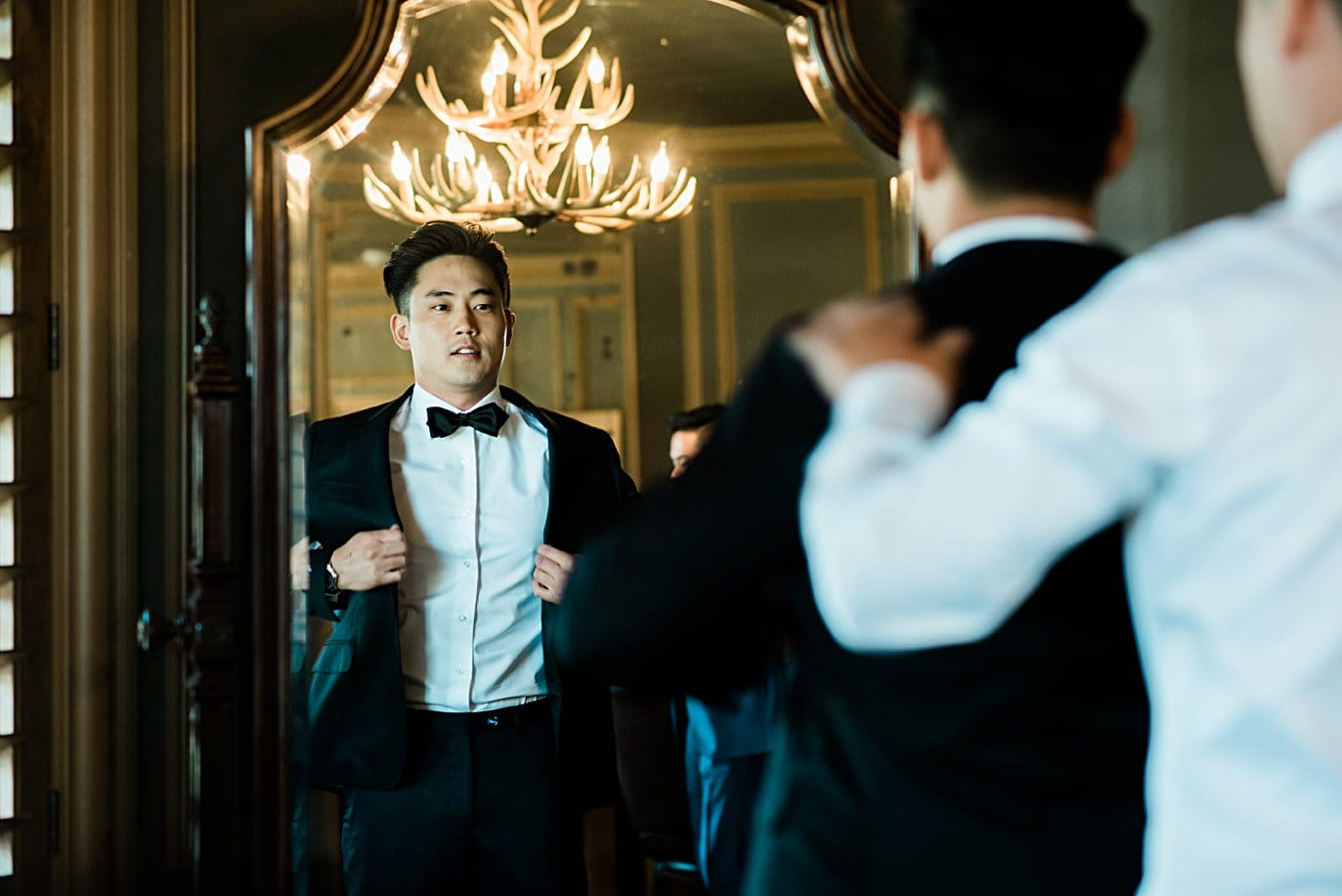 groom putting on tuxedo at Highlands Ranch Mansion wedding by Denver wedding photographer Jennie Crate