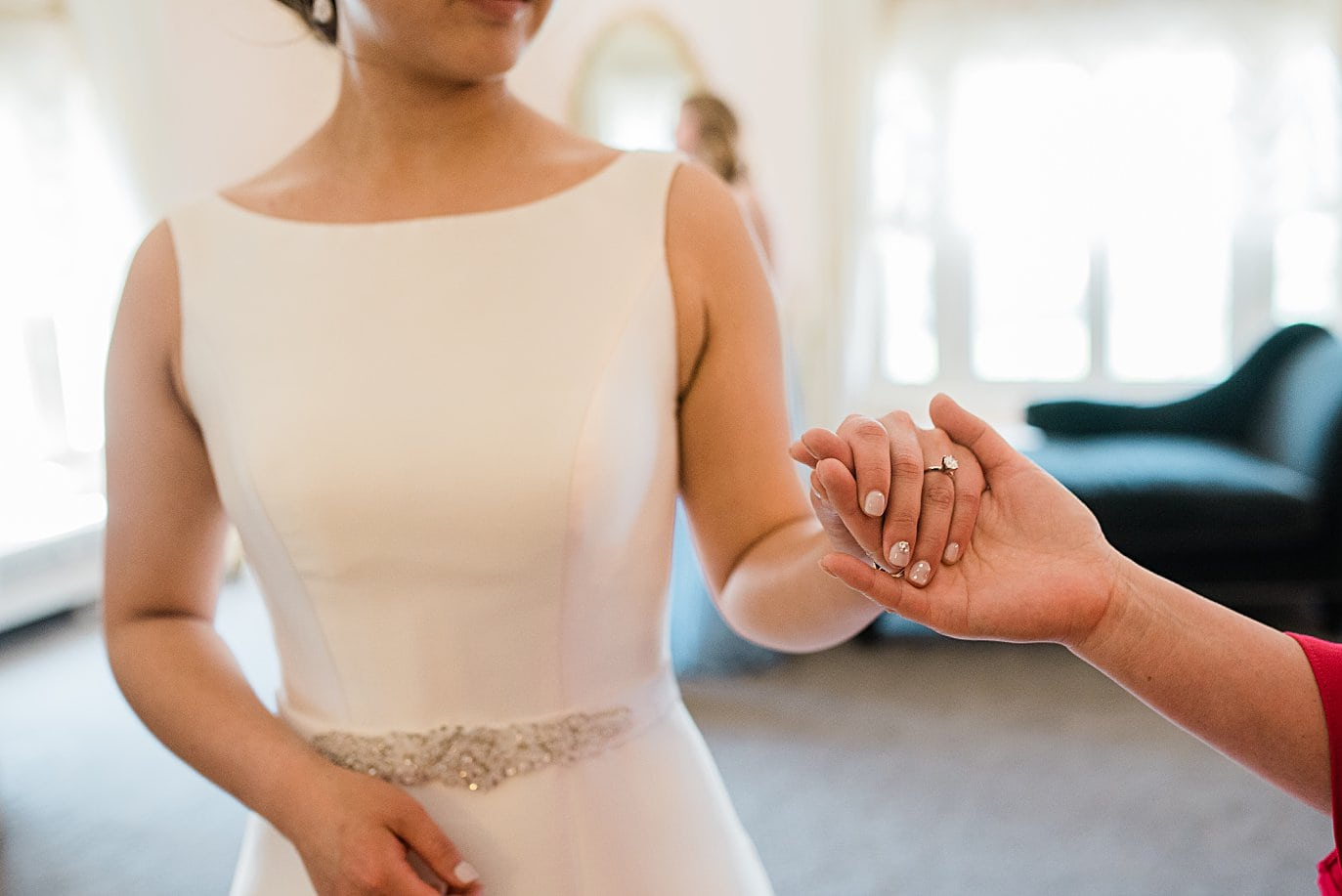 bride holds mom's hand before walking down aisle at Highlands Ranch Mansion wedding by Denver wedding photographer Jennie Crate
