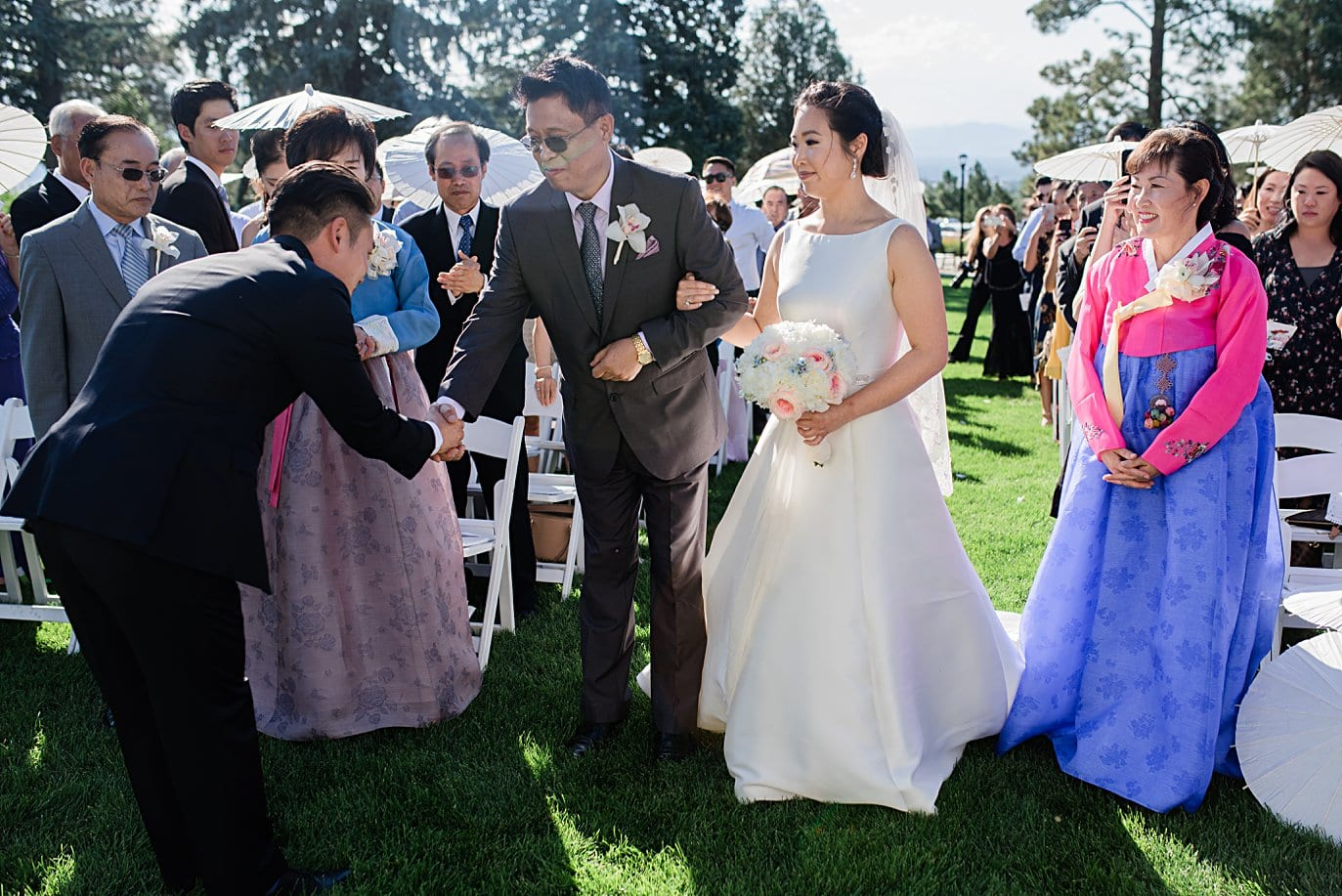 groom bows to brides dad before korean wedding ceremony at Highlands Ranch Mansion wedding by Golden wedding photographer Jennie Crate