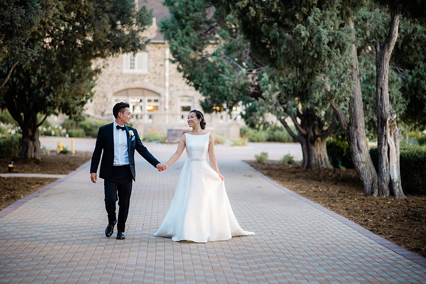 bride and groom walk on main driveway at Highlands Ranch Mansion wedding by Boulder wedding photographer Jennie Crate