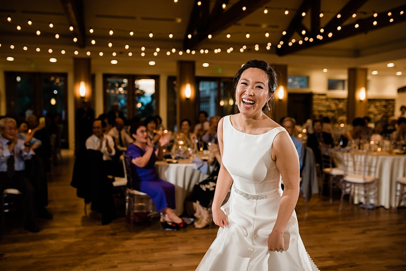 bride laughing on dance floor at Highlands Ranch Mansion wedding by Boulder wedding photographer Jennie Crate
