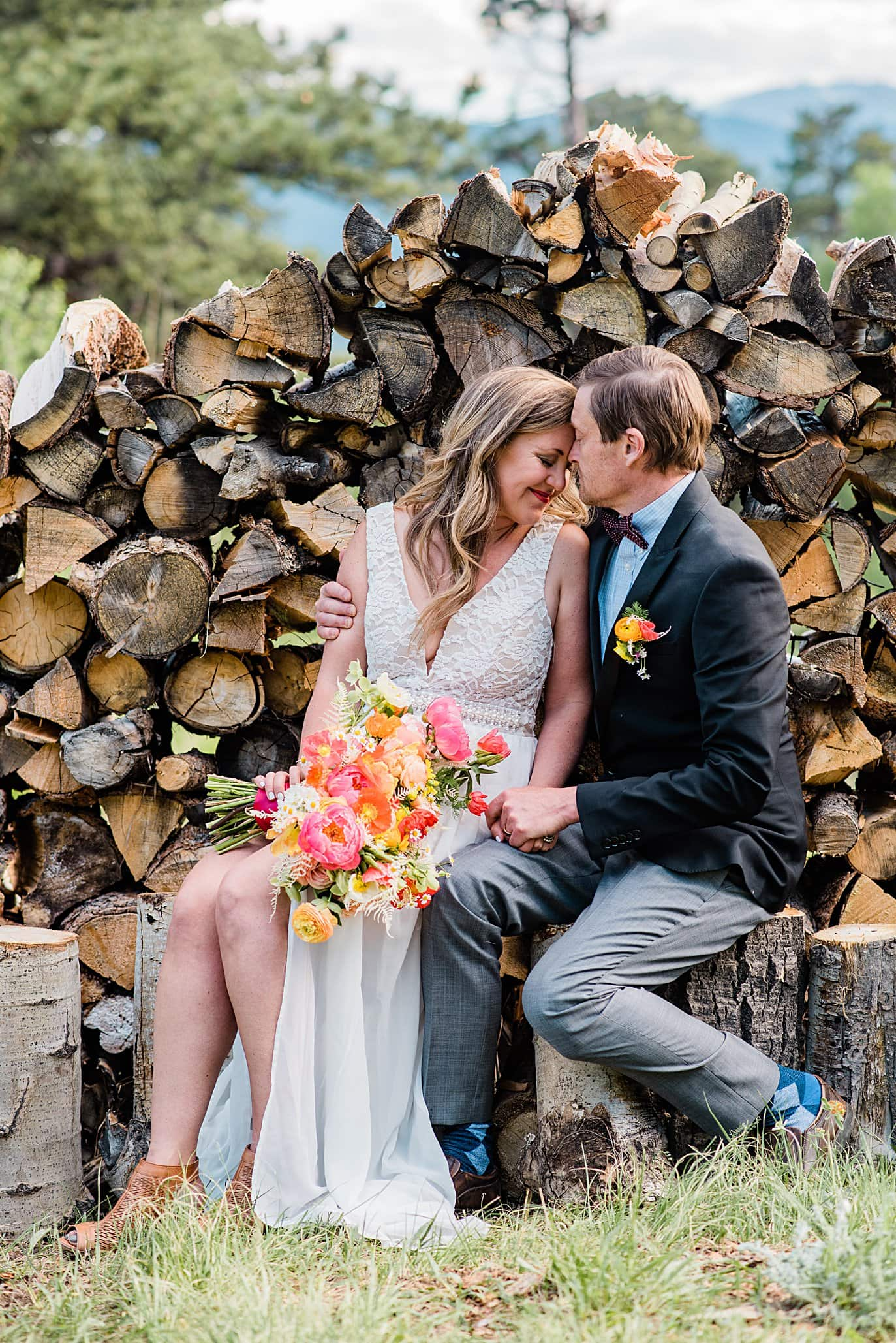 bride and groom cuddle by split log firewood pile at private property Golden elopement by Golden wedding photographer Jennie Crate