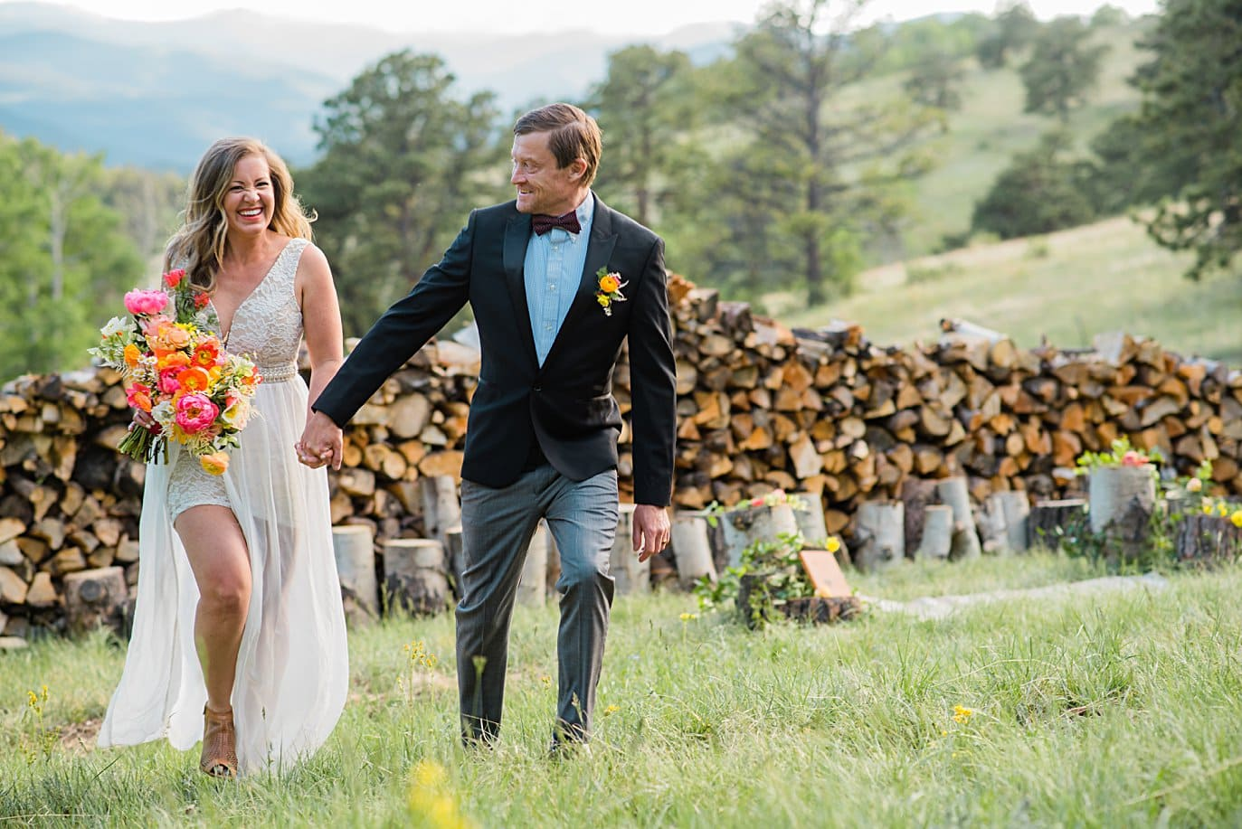 bride and groom walk hand in hand from outdoor ceremony at private Golden elopement by Boulder elopement photographer Jennie Crate