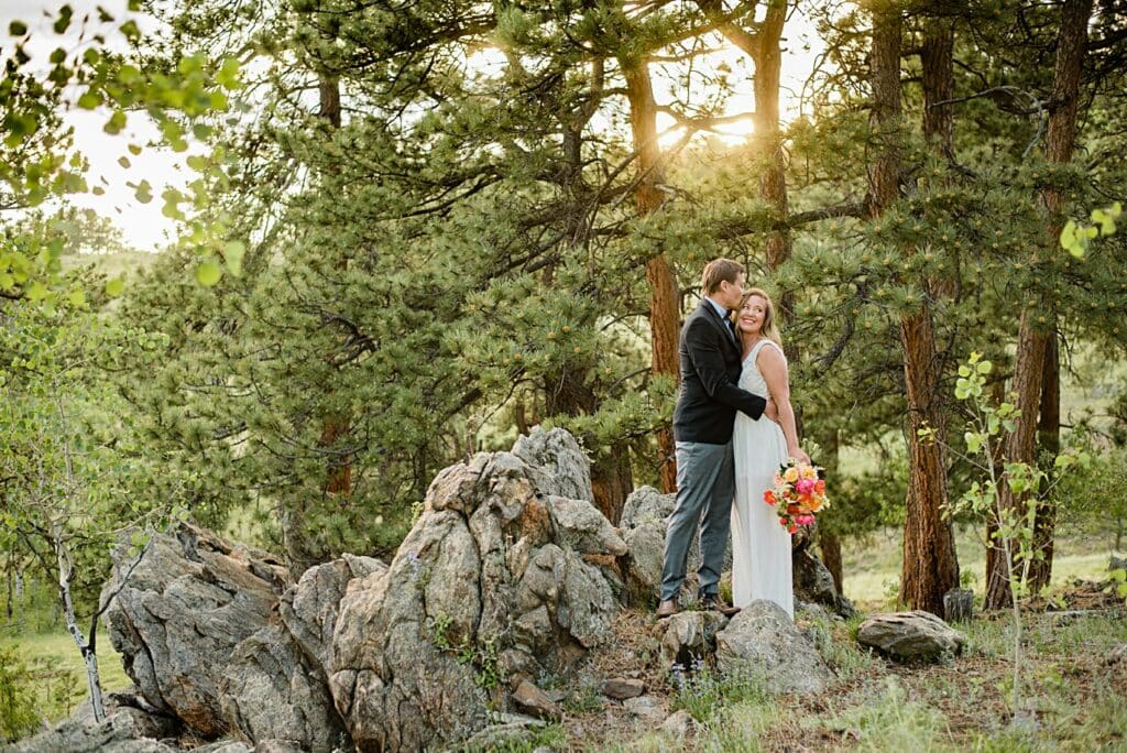 bride and groom cuddle by rock formations at Golden elopement by Golden elopement photographer Jennie Crate