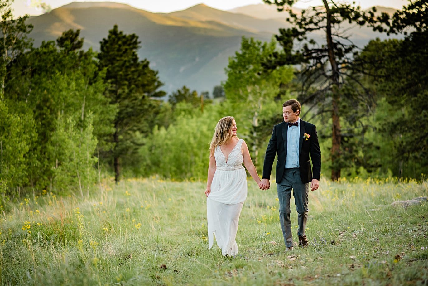 bride and groom walk hand in hand in field with mountain alpenglow at Golden elopement by Golden elopement photographer Jennie Crate