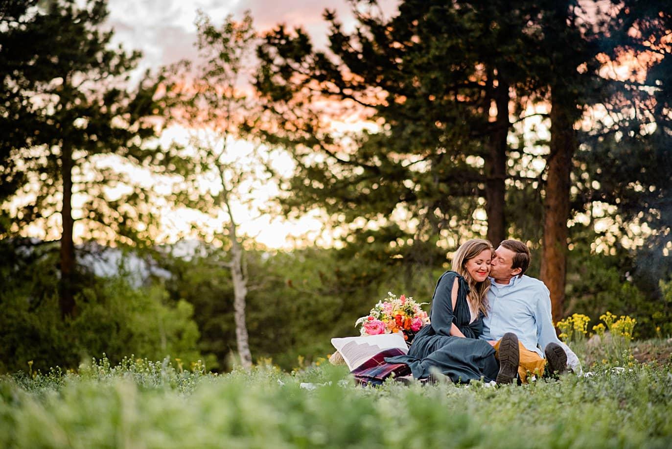couple cuddles in grass at sunset at Golden elopement by Golden elopement photographer Jennie Crate