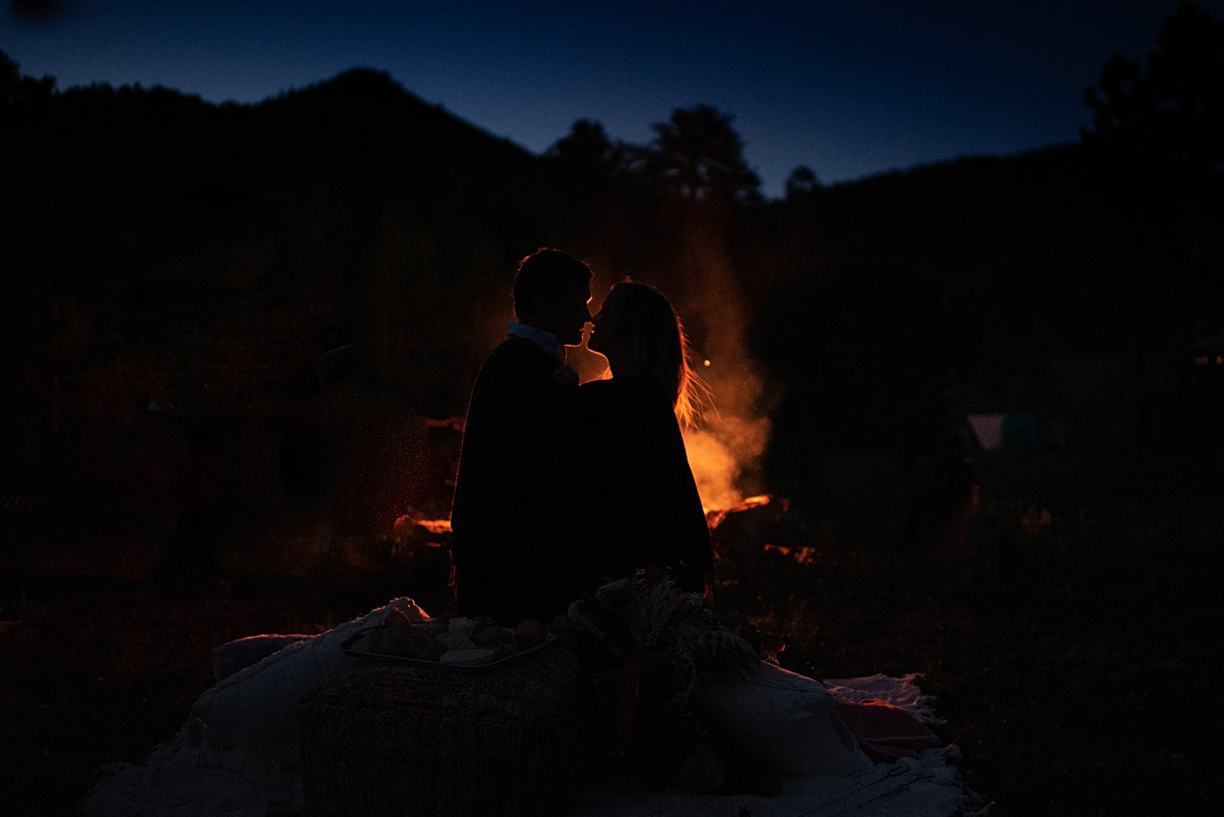 couple cuddled by firepit at private Golden elopement by Boulder wedding photographer Jennie Crate