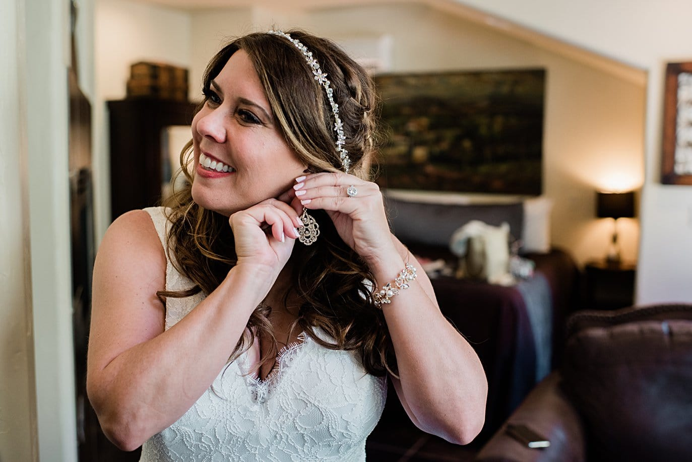 bride putting earrings on at Lily Lake Elopement by Estes Park elopement photographer Jennie Crate