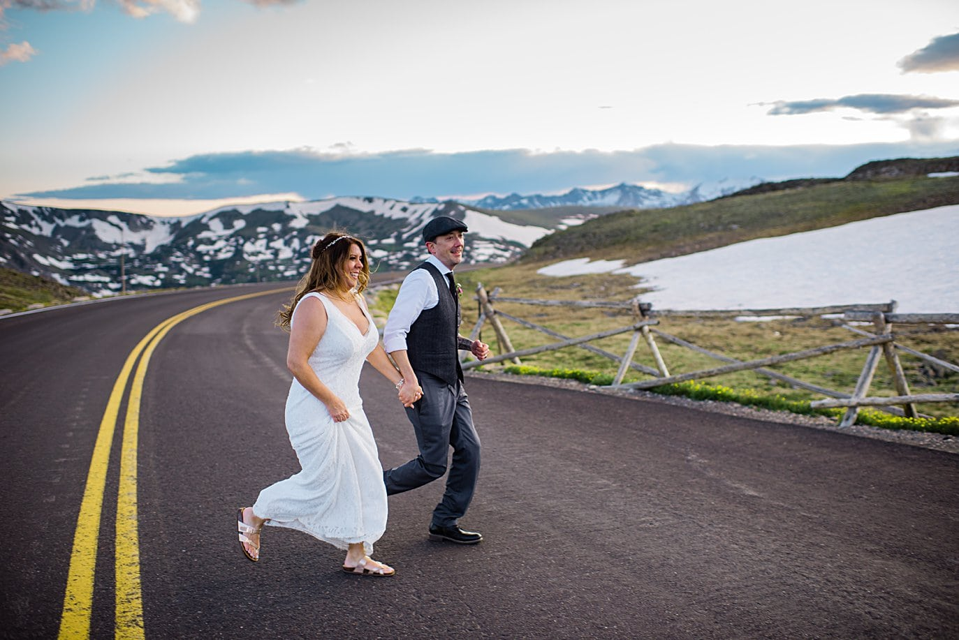 bride and groom run across road at Rocky Mountain National Park elopement by Boulder elopement photographer Jennie Crate