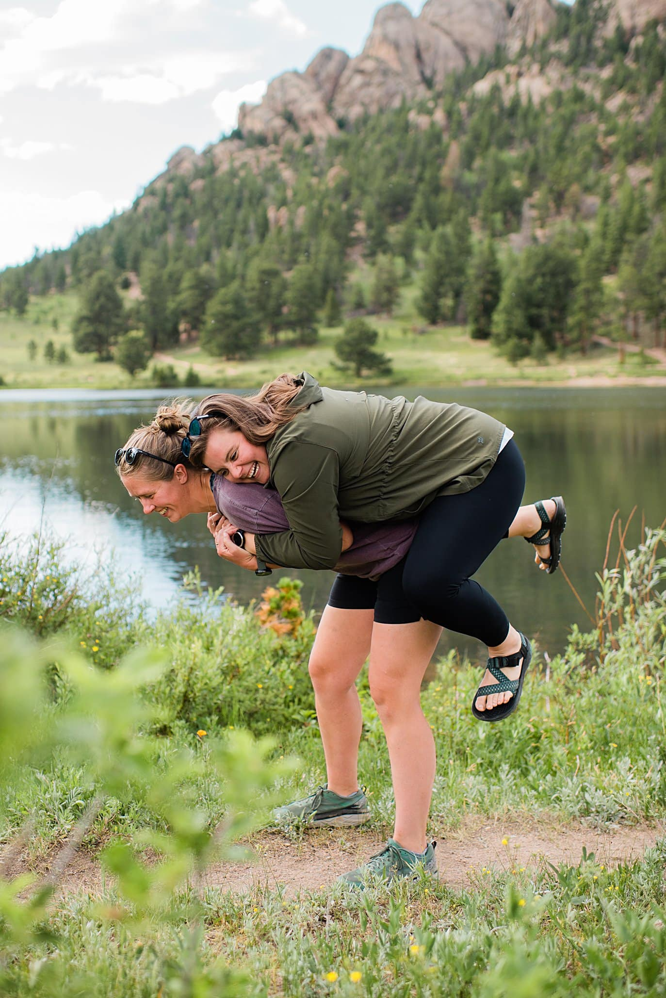 brides laughing and goofing off after wedding proposal at Estes Park Lily Lake by Estes Park wedding photographer Jennie Crate
