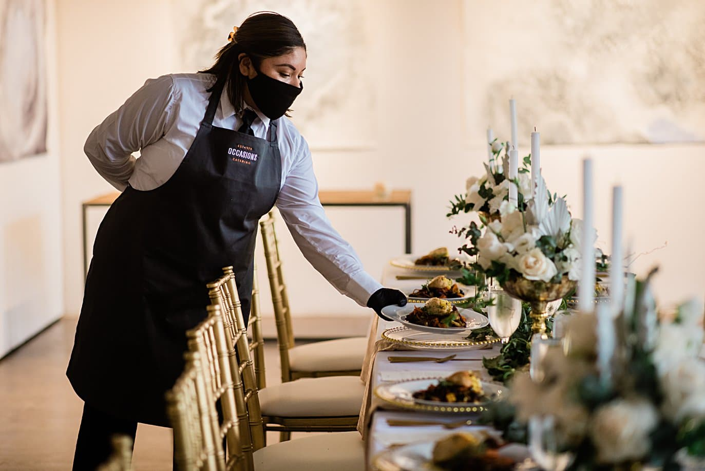 caterer serving meal at table wearing mask at Walker Fine Art Gallery Wedding by Boulder Wedding Photographer Jennie Crate