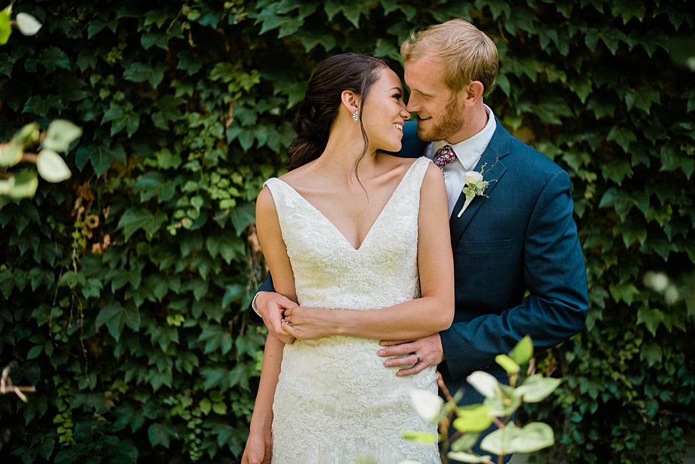 bride and groom cuddle by ivy wall at Walker Fine Art Gallery Wedding by Fort Collins Wedding Photographer Jennie Crate