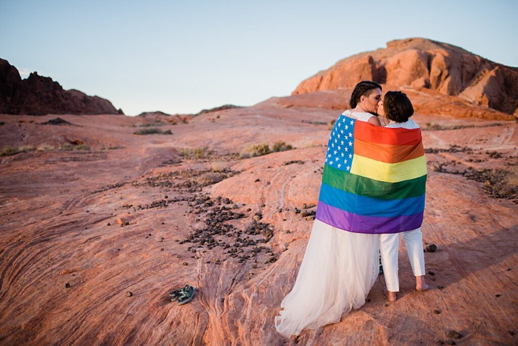 two brides wrapped in pride flag on wedding day at sunset in Valley of Fire Nevada at Valley of Fire wedding by Las Vegas wedding photographer Jennie Crate