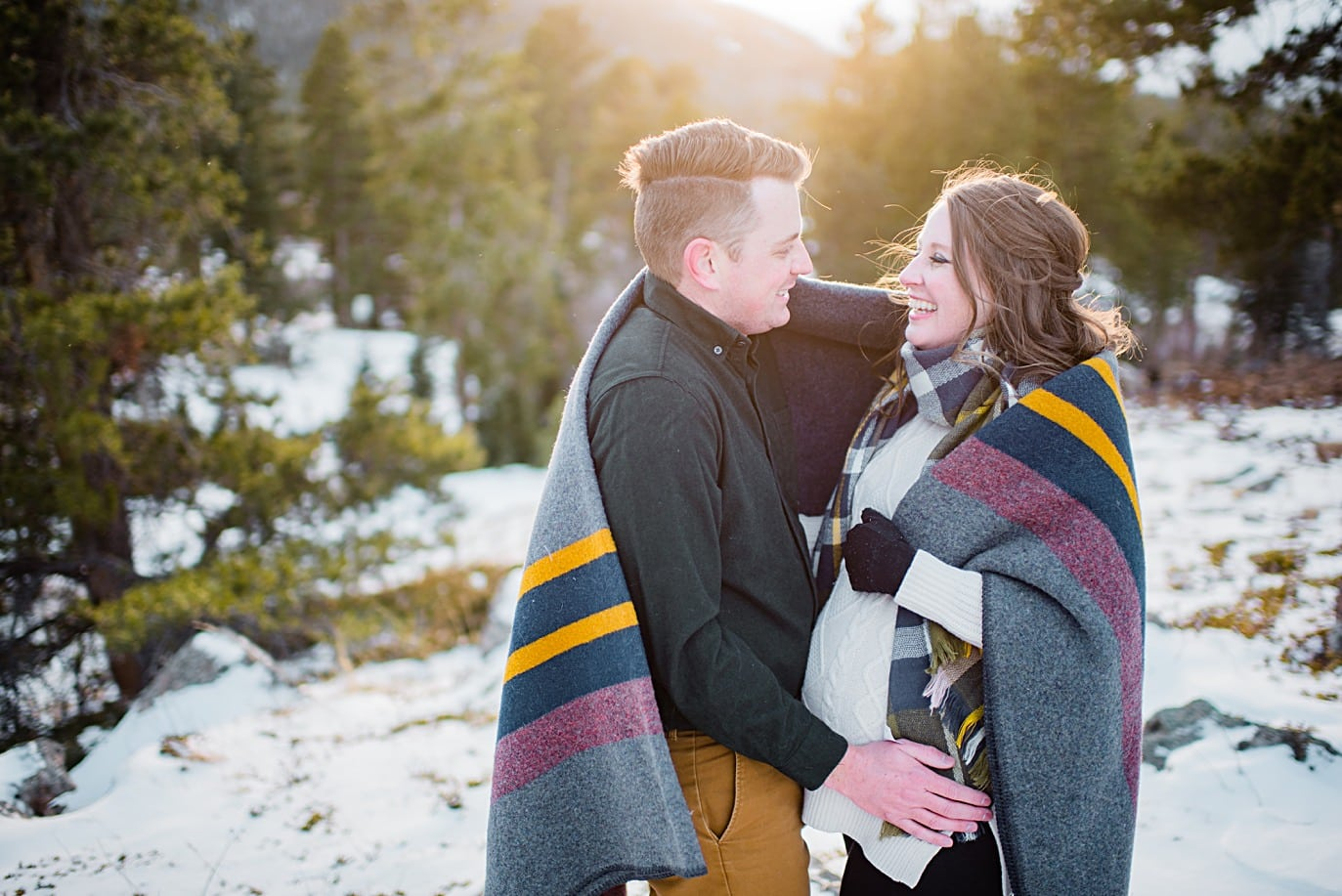 couple huddles under blanket during maternity session in Rocky Mountain National Park by Denver maternity photographer Jennie Crate