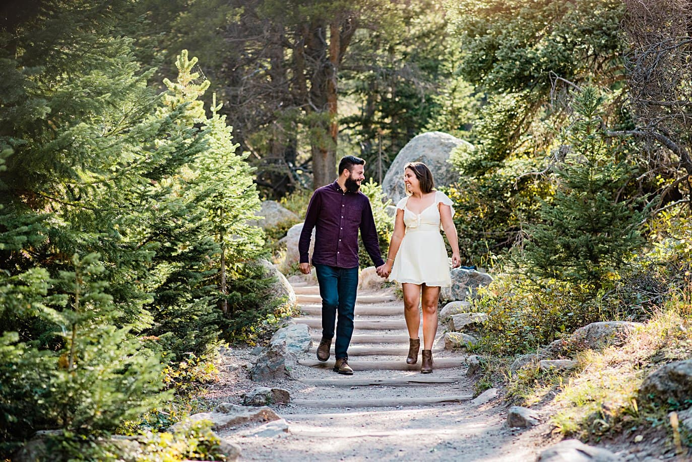 couple walking down trail at Alberta falls engagement session by Estes Park engagement photographer Jennie Crate