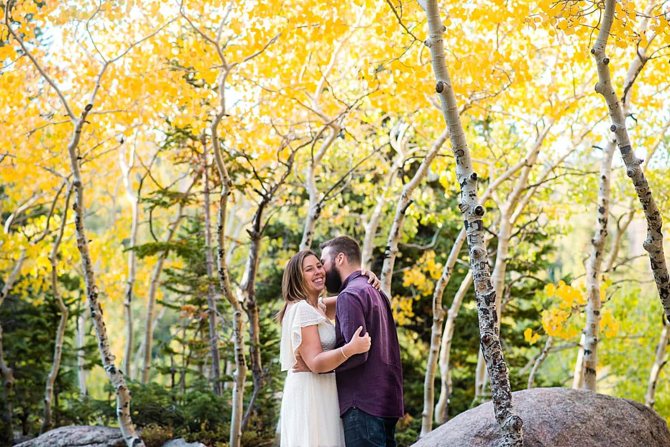 couple kisses in aspen grove in RMNP at Alberta falls engagement session by Estes Park engagement photographer Jennie Crate