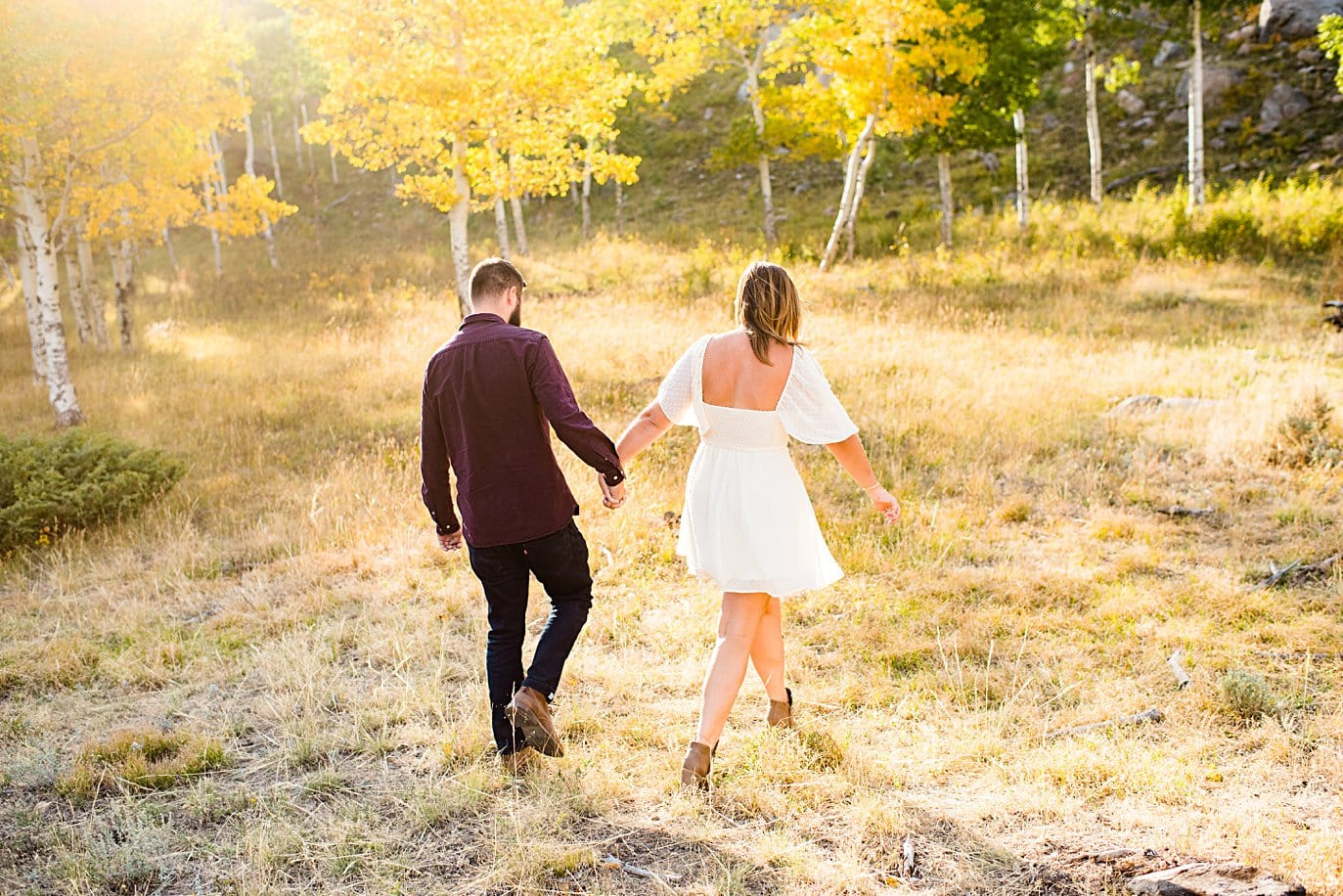 engaged couple walks in aspen grove in fall at RMNP engagement session by Estes Park engagement photographer Jennie Crate