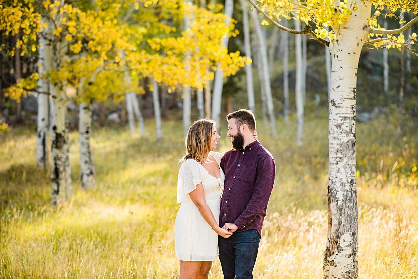 Couple in golden aspen grove couple walks in aspen grove in fall at RMNP engagement session by Boudler engagement photographer Jennie Crate