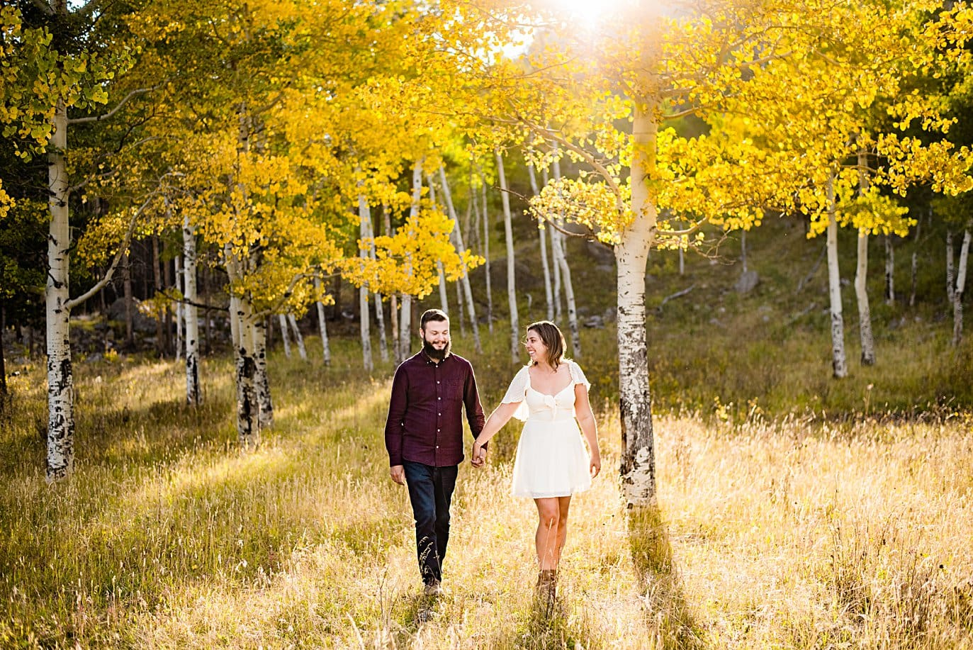 couple walks in sunshine in golden aspen grove at RMNP engagement session by Boudler engagement photographer Jennie Crate