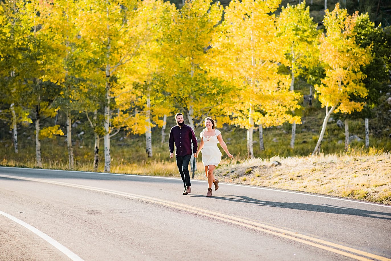 couple runs across the road in front of golden aspens at RMNP engagement session by Boudler engagement photographer Jennie Crate