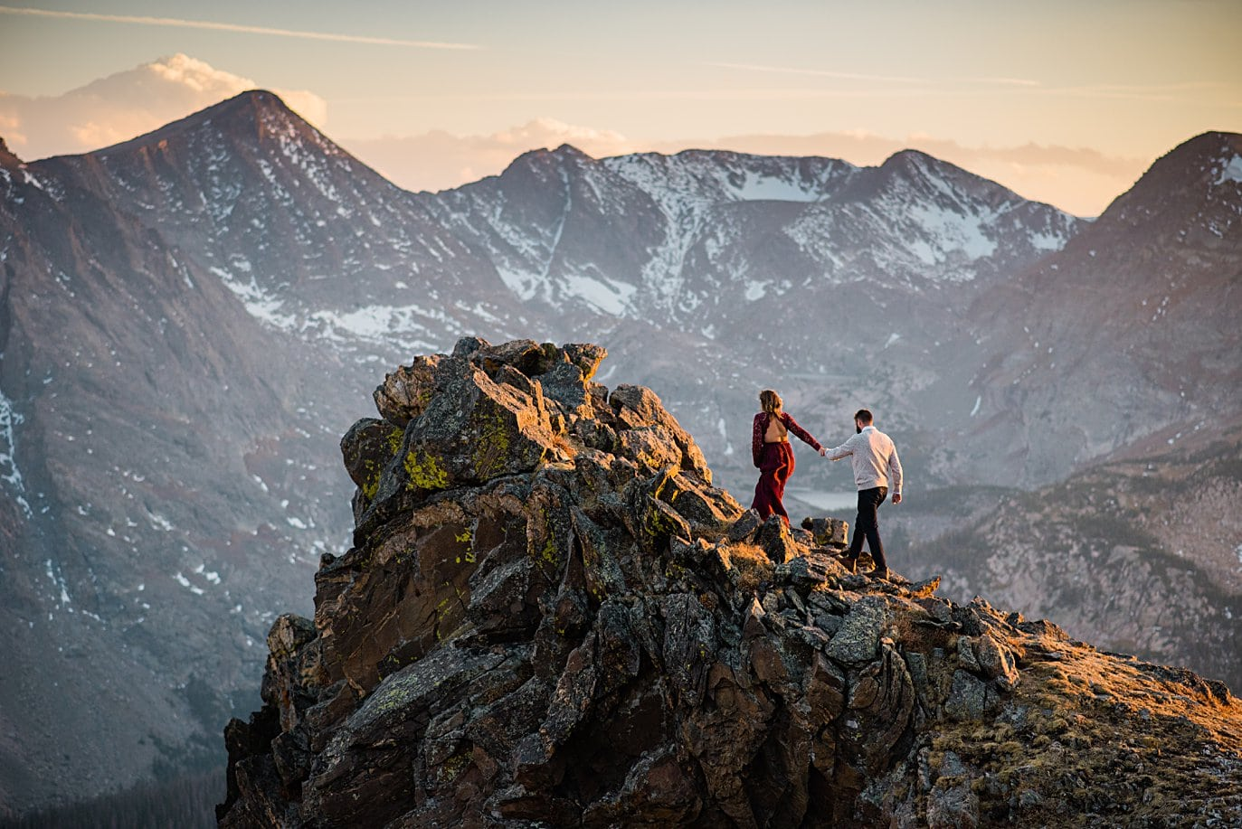 couple walking to top of rock at top of trail ridge road by Grand Lake engagement photographer Jennie Crate