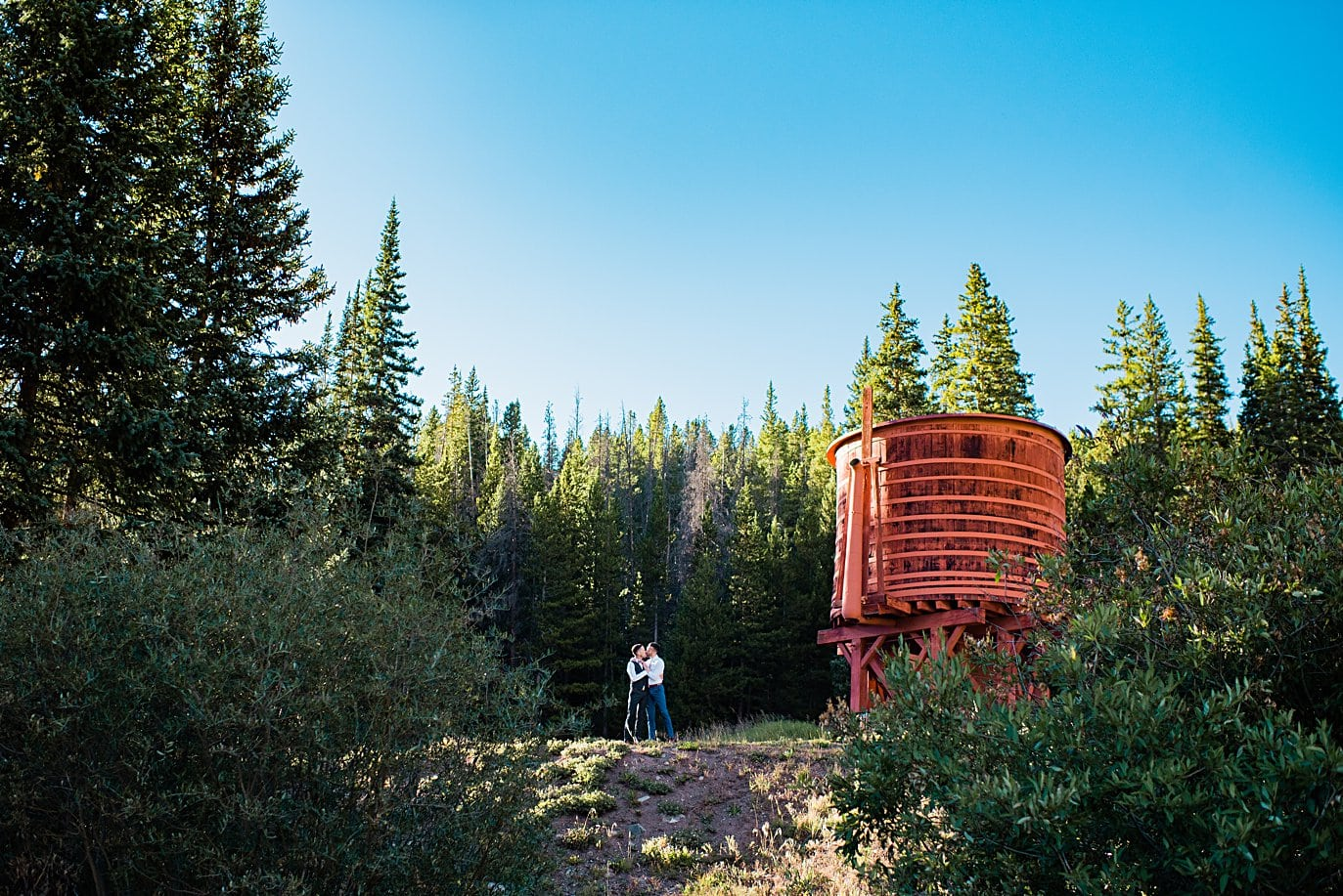 grooms by water tower before ceremony at Breckenridge Elopement by Colorado gay wedding photographer Jennie Crate