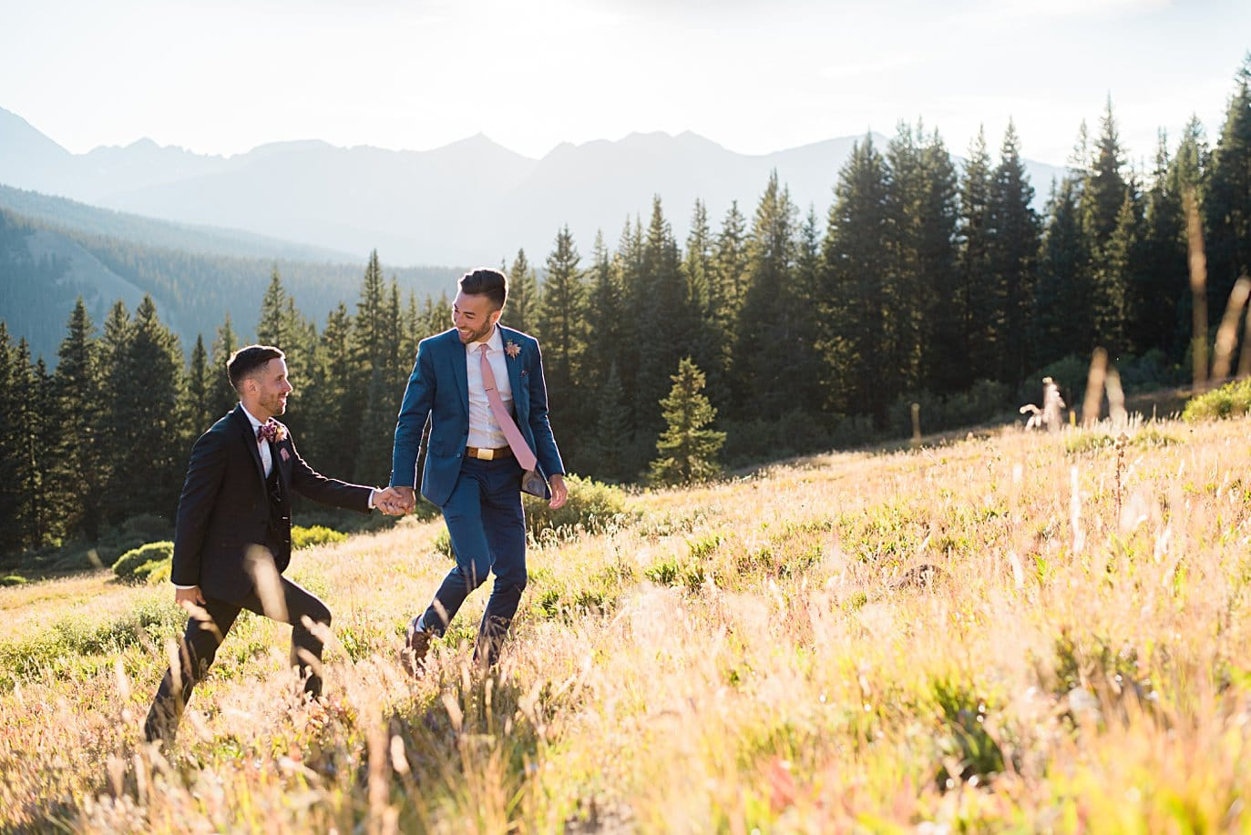 two grooms walk in meadow after self-solemnized ceremony at Breckenridge Elopement by Colorado gay wedding photographer Jennie Crate