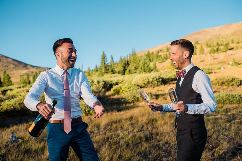 grooms toast with champagne at top of Boreas Pass at sunset by Denver Elopement photograpeher Jennie Crate
