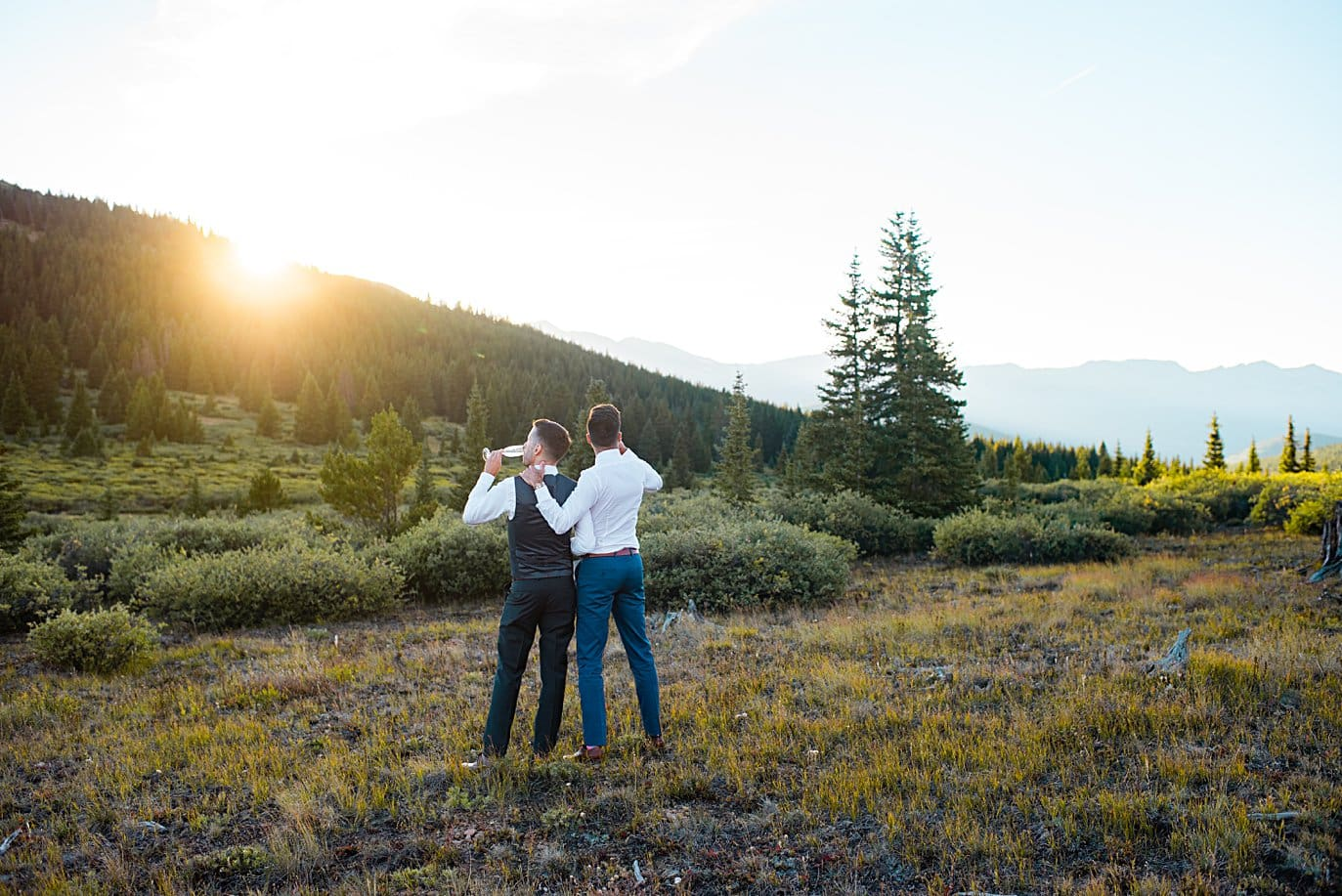grooms enjoy champagne at sunset at top of Boreas Pass at sunset by Denver Elopement photograpeher Jennie Crate