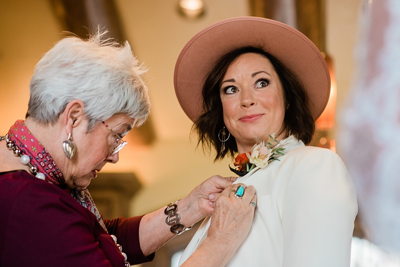 bride gets boutonniere pinned on white suit on wedding day at Boreas Pass microwedding by Breckenridge wedding photographer Jennie Crate