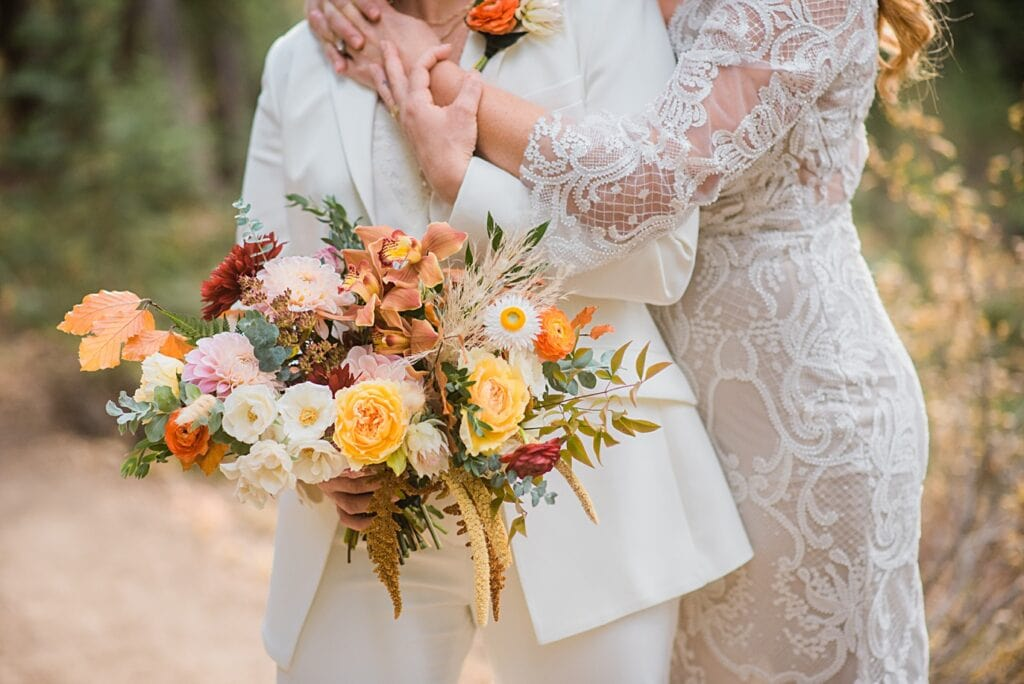 bride in dress with bride in suit and colorful bridal bouquet at Breckenridge microwedding by Colorado LGBT wedding photographer Jennie Crate