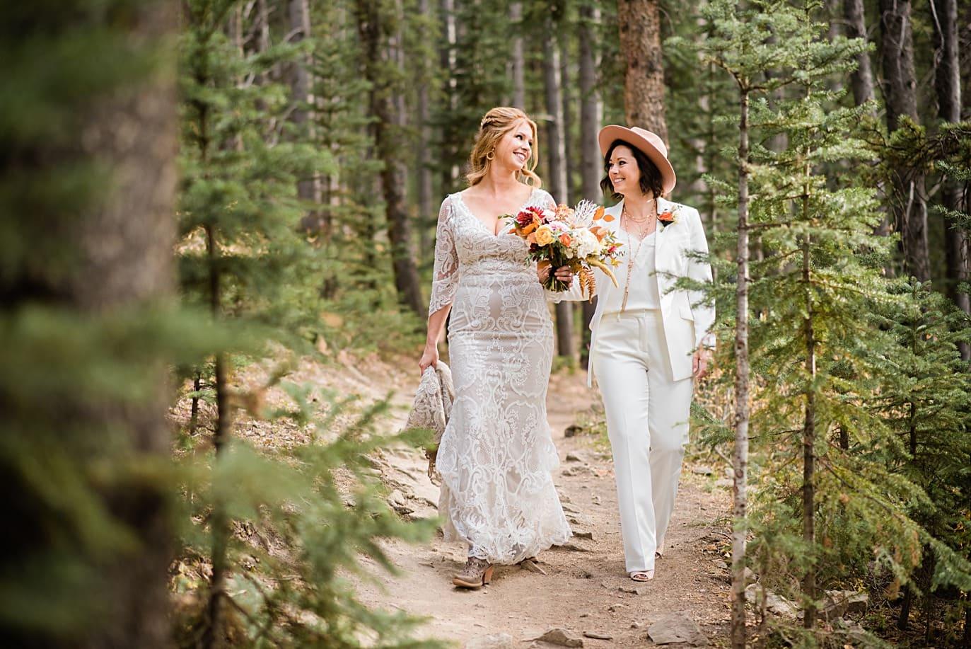 two brides walk through woods at Breckenridge microwedding by Colorado LGBT wedding photographer Jennie Crate