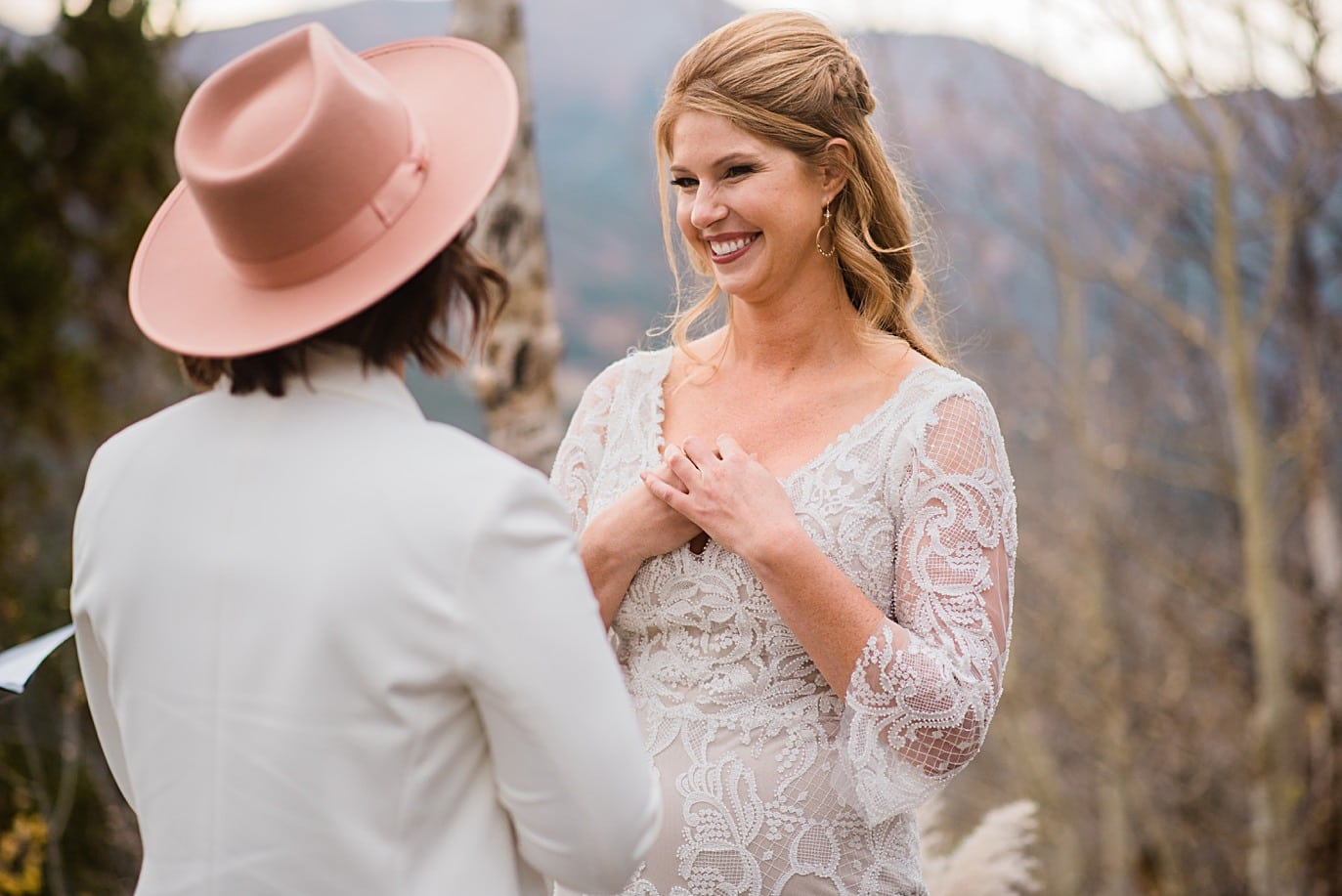 brides warm rings during intimate wedding ceremony at Boreas Pass microwedding by Colorado gay wedding photographer Jennie Crate
