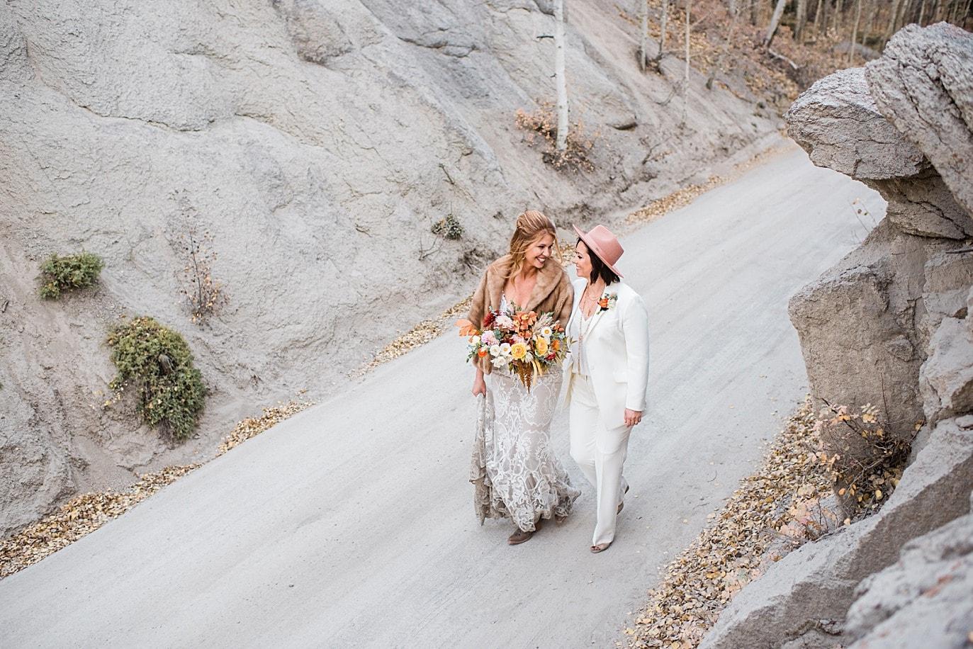 two brides walk along road two brides along Boreas Pass road at Breckenridge microwedding by Breckenridge wedding photographer Jennie Crate