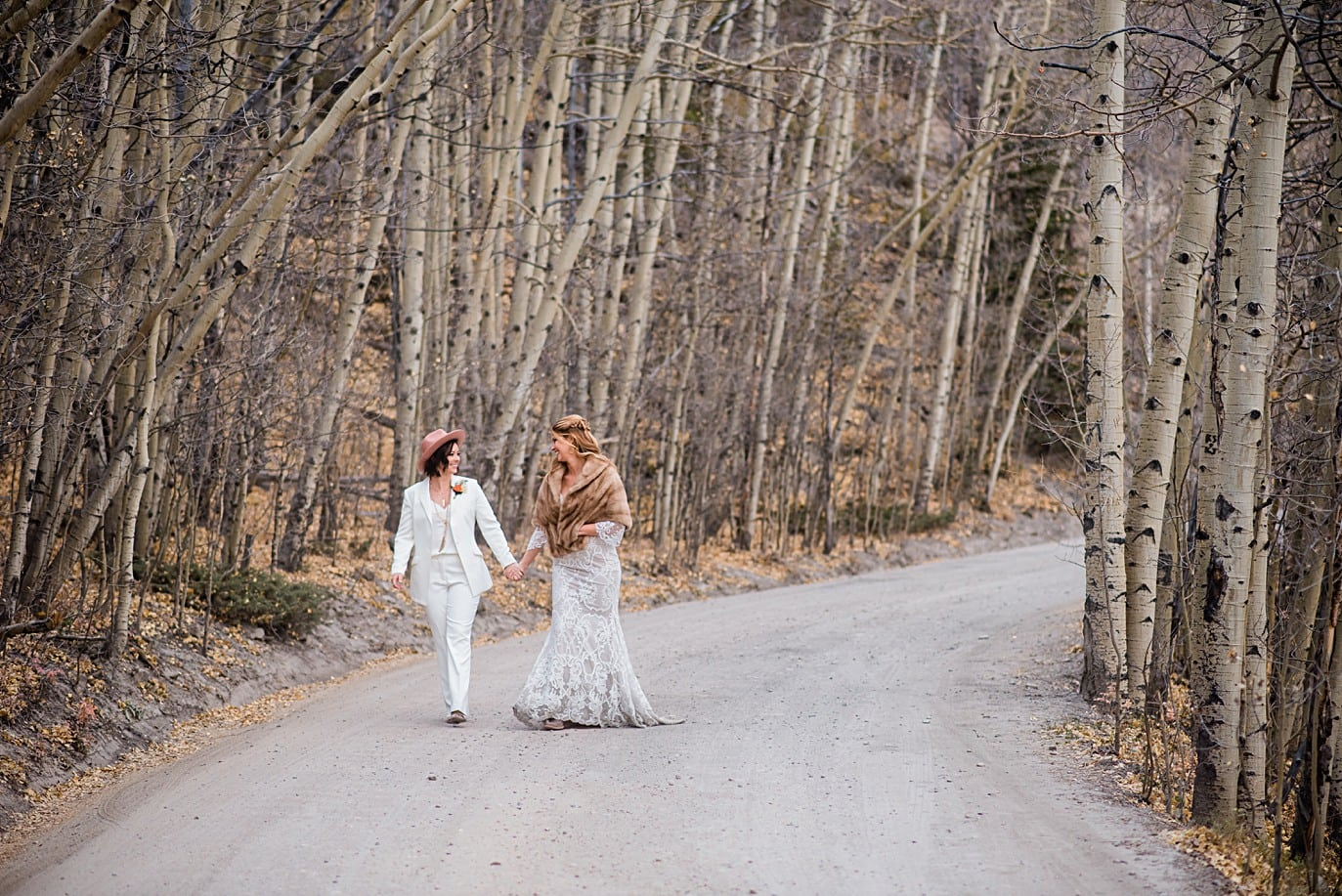 brides in bare aspen trees two brides along Boreas Pass road at Breckenridge microwedding by Breckenridge wedding photographer Jennie Crate