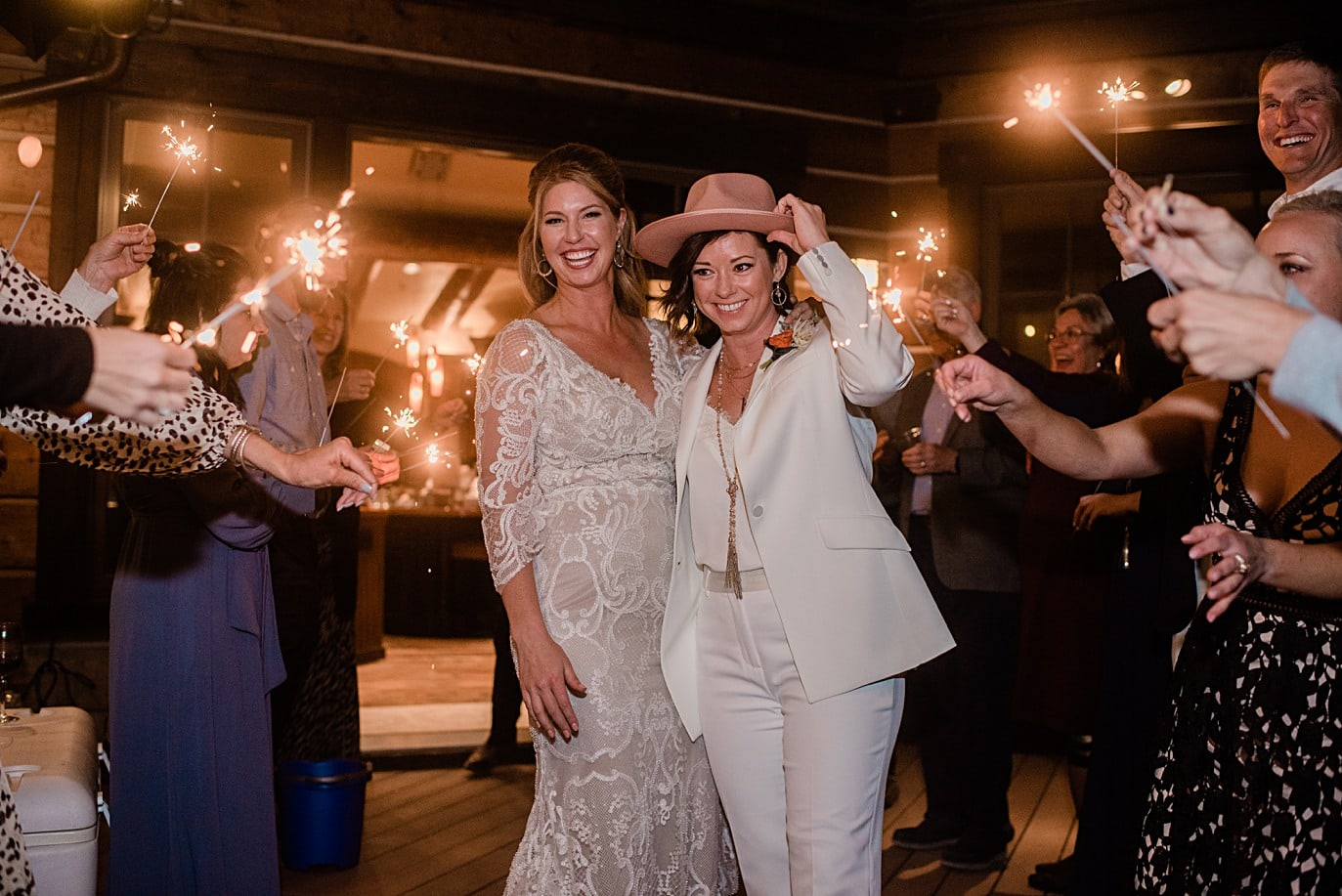 two brides at sparkler exit bride gets into custom lace dress at Boreas Pass microwedding by Breckenridge wedding photographer Jennie Crate